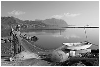 Fisherman pulling out net out of small baot, Kaneohe Bay, morning. Oahu island, Hawaii, USA ( black and white)