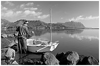 Fisherman pulling out fish out a net, with girl looking, Kaneohe Bay, morning. Oahu island, Hawaii, USA ( black and white)