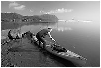 Man loading sea kayak for a fishing trip, Kaneohe Bay, morning. Oahu island, Hawaii, USA (black and white)