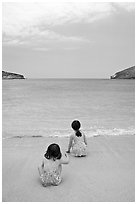 Two girls at the edge of water, Hanauma Bay. Oahu island, Hawaii, USA ( black and white)