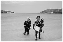 Scuba divers walking out of the water, Hanauma Bay. Oahu island, Hawaii, USA ( black and white)