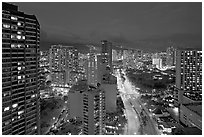 Boulevard and high-rise towers at dusk. Waikiki, Honolulu, Oahu island, Hawaii, USA (black and white)
