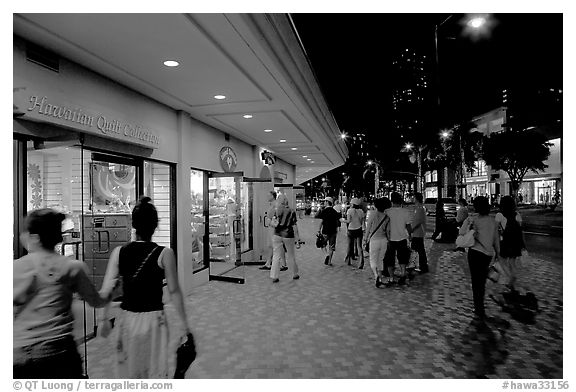 Shops on Kalakaua avenue at night. Waikiki, Honolulu, Oahu island, Hawaii, USA (black and white)