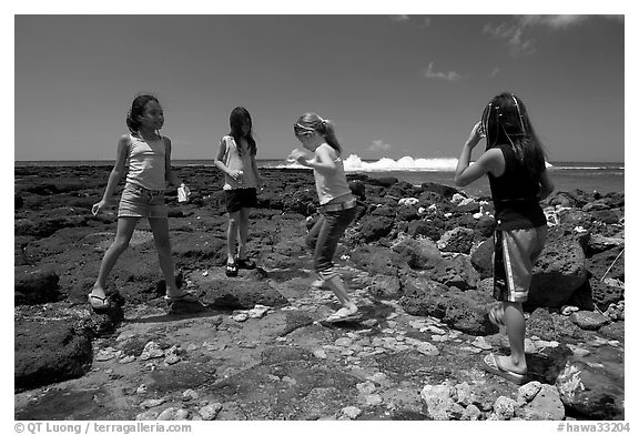 Girls playing in tidepool, Kukuila. Kauai island, Hawaii, USA