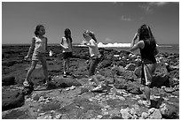 Girls playing in tidepool, Kukuila. Kauai island, Hawaii, USA (black and white)