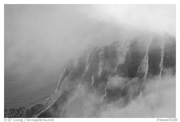 Fluted ridges seen through clouds, Kalalau lookout, late afternoon. Kauai island, Hawaii, USA (black and white)