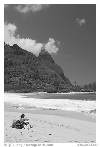 Woman sitting on a beach chair on Tunnels Beach. North shore, Kauai island, Hawaii, USA (black and white)