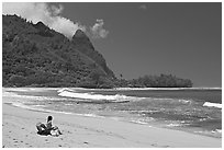 Woman sitting on a beach chair on Makua (Tunnels) Beach. North shore, Kauai island, Hawaii, USA (black and white)
