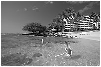 Children on Puu Poa Beach and Princeville Hotel. Kauai island, Hawaii, USA (black and white)