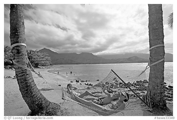 Family on Hammock with Hanalei Bay in the background. Kauai island, Hawaii, USA (black and white)