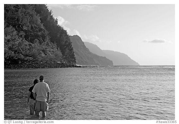 Couple standing in water, Kee Beach, late afternoon. Kauai island, Hawaii, USA (black and white)