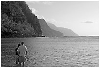 Couple standing in water, Kee Beach, late afternoon. Kauai island, Hawaii, USA ( black and white)