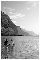 Couple looking at the Na Pali Coast, Kee Beach, late afternoon. Kauai island, Hawaii, USA ( black and white)