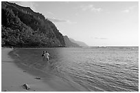 Couple standing in water looking at the Na Pali Coast, Kee Beach, late afternoon. Kauai island, Hawaii, USA (black and white)