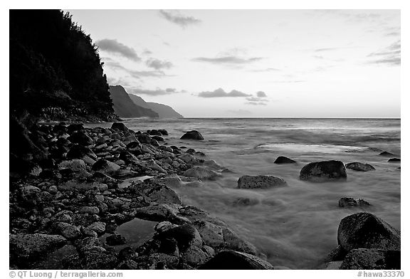 Boulders, waves, and Na Pali Coast, sunset. North shore, Kauai island, Hawaii, USA (black and white)
