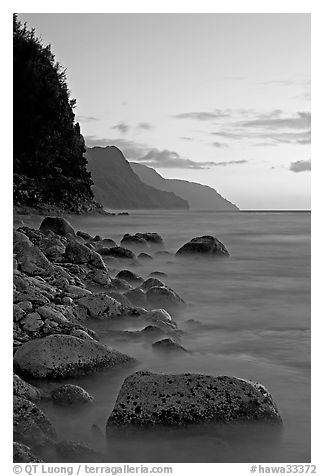 Boulders, surf, and Na Pali Coast, sunset. Kauai island, Hawaii, USA (black and white)