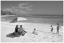 Couple sitting under sun unbrella with children playing around, Poipu Beach, mid-day. Kauai island, Hawaii, USA (black and white)