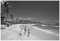 Children playing around, Kiahuna Beach, mid-day. Kauai island, Hawaii, USA (black and white)
