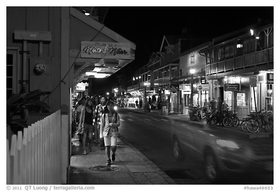 Tourists strolling store-lined street at night. Lahaina, Maui, Hawaii, USA (black and white)