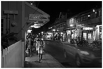 Tourists strolling store-lined street at night. Lahaina, Maui, Hawaii, USA ( black and white)