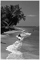 Surfer walking on beach. Lahaina, Maui, Hawaii, USA (black and white)