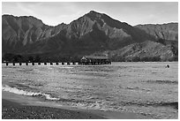 Hanalei Pier and surfer, early morning. Kauai island, Hawaii, USA (black and white)