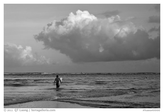 Surfer heading out in ocean. Kauai island, Hawaii, USA (black and white)