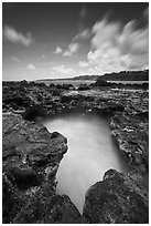 Surf in blowhole, Mokolea lava shelf. Kauai island, Hawaii, USA (black and white)