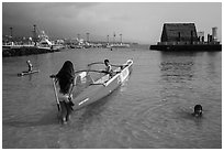 Girls, outrigger canoe, and Kamakahonu heiau, Kailua-Kona. Hawaii, USA (black and white)