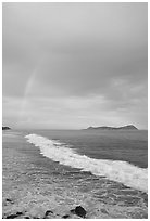 Rainbow at sunset, wave, and Aunuu island. Aunuu Island, American Samoa (black and white)
