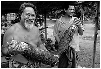Islanders holding Taro roots in Iliili. Tutuila, American Samoa (black and white)