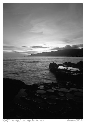Water-filled  grinding stones holes (foaga) and Leone Bay at sunset. Tutuila, American Samoa (black and white)