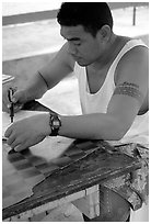 Young man drawing an artwork based on traditional siapo designs. Pago Pago, Tutuila, American Samoa ( black and white)