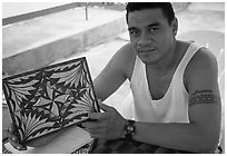 Young man showing an artwork based on traditional siapo designs. Pago Pago, Tutuila, American Samoa (black and white)