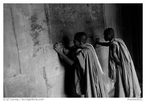 Two buddhist monks examine  bas-reliefs in Angkor Wat. Angkor, Cambodia (black and white)