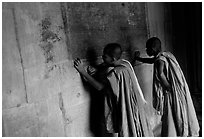 Two buddhist monks examine  bas-reliefs in Angkor Wat. Angkor, Cambodia ( black and white)