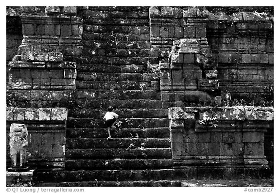Boy climbs near-vertical staircase, Angkor Thom complex. Angkor, Cambodia (black and white)