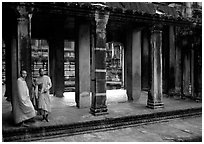 Two Buddhist monks in dark temple, Angkor Wat. Angkor, Cambodia ( black and white)