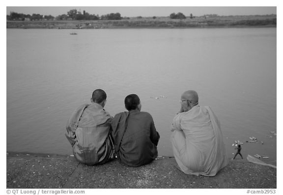 Buddhist monks sit on  banks of Tongle Sap river at dusk,  Phnom Phen. Cambodia (black and white)