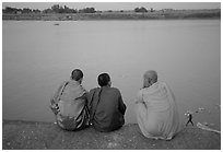 Buddhist monks sit on  banks of Tongle Sap river at dusk,  Phnom Phen. Cambodia ( black and white)