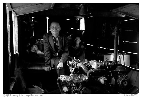 Engine and pilot at the rear of a slow passenger boat. Mekong river, Laos (black and white)