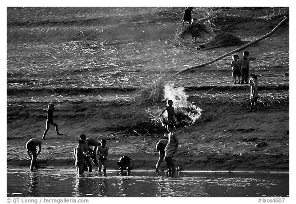 Children bathe in the river and dry out near a fire in a small hamlet. Mekong river, Laos