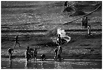 Children bathe in the river and dry out near a fire in a small hamlet. Mekong river, Laos (black and white)