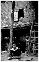 Children near stilt house of a small hamlet. Mekong river, Laos (black and white)