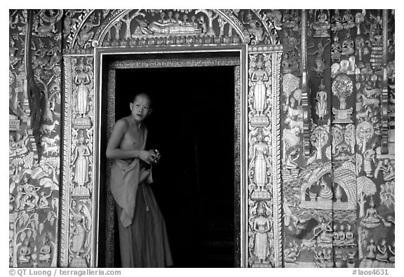 Buddhist novice monk stands at door of shrine, Wat Xieng Thong. Luang Prabang, Laos (black and white)