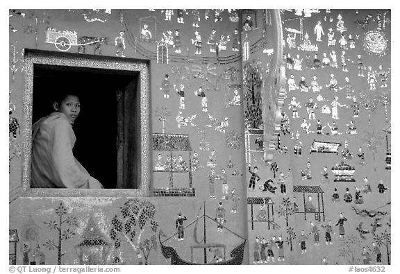 Buddhist novice monk sits at window of shrine, Wat Xieng Thong. Luang Prabang, Laos (black and white)