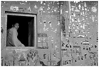 Buddhist novice monk sits at window of shrine, Wat Xieng Thong. Luang Prabang, Laos ( black and white)