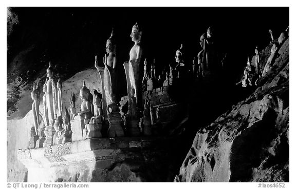 Hundreds of wooden Buddhist figures on wall shelves, Pak Ou caves. Laos (black and white)