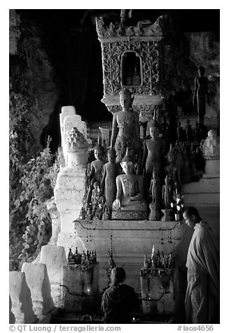 Novice Buddhist monk and vistor in Pak Ou cave. Laos (black and white)