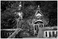 Novice Buddhist monk at entrance of cave, Pak Ou. Laos ( black and white)